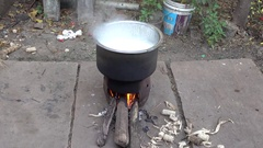 Old Village Stove Firing Woods and Making Milk Hot 4K Footage Stock Footage