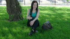 Pretty woman sitting on green grass with fashion handbag and looking to camera Stock Footage