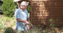Older man watering plants with hose (slow motion) Stock Footage