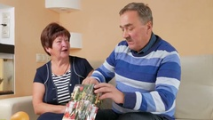 Happy senior man gives a woman's gift in package. He pulls out a pearl necklace Stock Footage