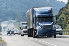 Blue Semi-Truck With Other Traffic On Interstate Highway Stock Photos