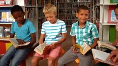 Teacher teaching kids in library Stock Footage