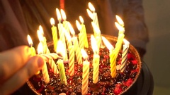 Closeup. Woman lights candles on tasty birthday cake. Prepearing for party Stock Footage
