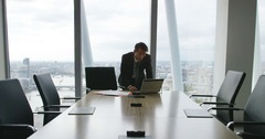 4k, Tired and stressed businessman in a boardroom all by himself. Slow motion. Stock Footage