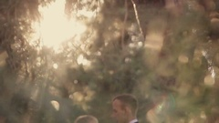 Groom embraces the bride in a park in the sunshine Stock Footage