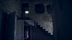Ghost girl in white dress wandering the corridors of an abandoned house Stock Footage