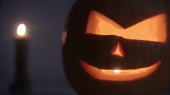 Carved Halloween pumpkin lights inside with flame on a dark blue background with Stock Footage