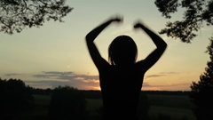 Young woman jumping and dancing in the forest after sunset Stock Footage