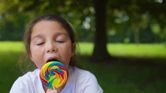 4K Portrait of happy little girl eating lollipop outdoors in natural setting Stock Footage