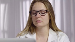 Young woman in a lab coat working at her computer Stock Footage