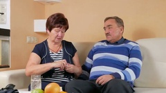 An older woman gives a pill with a glass of water to her husband at home on the Stock Footage