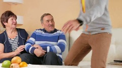 Adult son comes to visit elderly father and mother in the home. Everyone is Stock Footage