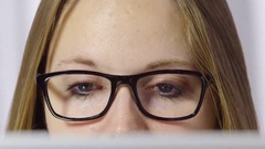 Close up of young woman's eyes looking at computer screen Stock Footage