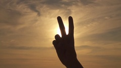 CLOSE UP: Making peace or V sign over stormy sky and golden summer sunshine Stock Footage