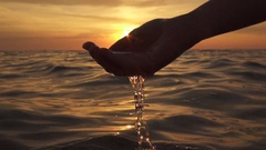 SLOW MOTION: Scooping water with fingers and pouring it into the ocean at sunset Stock Footage