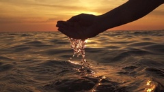 SLOW MOTION: Scooping water with fingers and pouring it into the sea at sunset Stock Footage