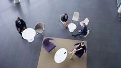 4K Overhead view business group in meeting area of large modern office building Stock Footage