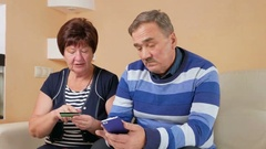Senior couple shopping in internet shop by credit card and phone. Man and woman Stock Footage