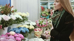 Beautiful girl with long hair choose a bouquet Stock Footage