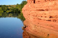 Riverbank Tosna of red sandstone. Stock Photos