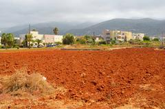 View of red arable land, Malia town and mountain. Stock Photos