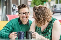 Cute lesbian couple joking outside at bistro Stock Photos