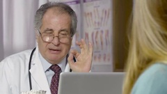 Doctor consulting with patient about prescription drugs Stock Footage