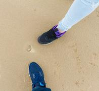 Boy and girl legss,  sports shoes and sea-shell on sand Stock Photos