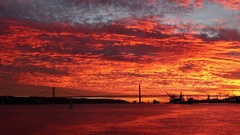 Fabulous bloody sunset over Tagus river over 25th April Bridge Lisbon Stock Footage