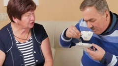 Happy senior man and woman talking at home over a cup of coffee. Husband and Stock Footage