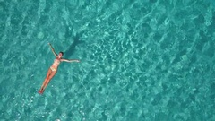 Aerial - Adult woman floating on water Stock Footage