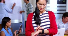 Female business executive adjusting time on smartwatch while coworker working in Stock Footage