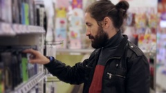 Men with beard and long hair selecting antiperspirant in supermarket. Stock Footage