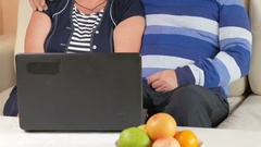 Happy senior man and a woman watching the movie on the laptop. They hug and Stock Footage