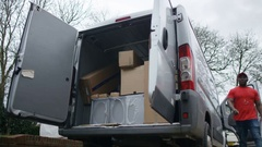 4K Delivery driver unloading boxes from the back of van Stock Footage