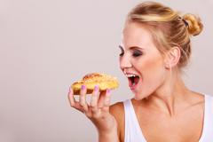 Undecided woman holds cake sweet bun in hand Stock Photos