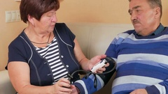 Elderly woman measures the blood pressure at home on the couch. Poor man's well Stock Footage