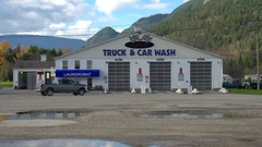 Generic transport truck passes in front of generic car and truck wash Stock Footage