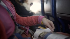Female passenger reading airline magazine during flight on board of airplane Stock Footage