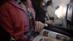 Young woman turning pages of glossy magazine while flying by passenger plane Stock Footage