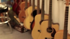 Pan to acoustic guitars on wall rack Stock Footage