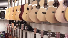 Tilt pan down row of acoustic guitars Stock Footage
