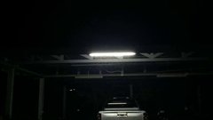 Garage in the dark and fluorescent light with small insects flying around Stock Footage