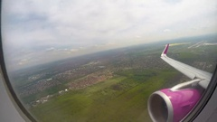 POV of flight passenger looking through window at ground, sky and aircraft wing Stock Footage