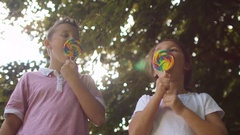 4K Portrait of happy little boy & girl eating lollipops outdoors Stock Footage