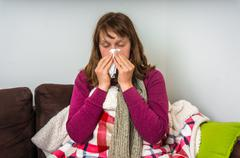 Sick woman having flu and blowing her runny nose at handkerchief Stock Photos