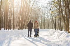 Happy young family walking in the park in winter. The parents carry the baby in Stock Photos