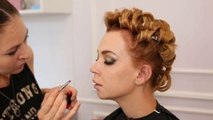 Professional makeup artist putting cosmetics on model face Stock Footage