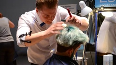 Male hairdressers making male haircut Stock Footage