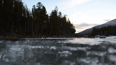 Cold mountain creek water and massive clear ice buildup dam with forest and sky  Stock Footage